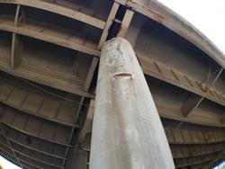 Corroding and rusting concrete pillars on a bridge.