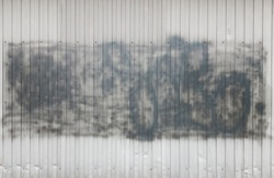 Corrugated metal corrugated wall with black spray paint, shading material. Gray background with copy space, crumpled iron slate
