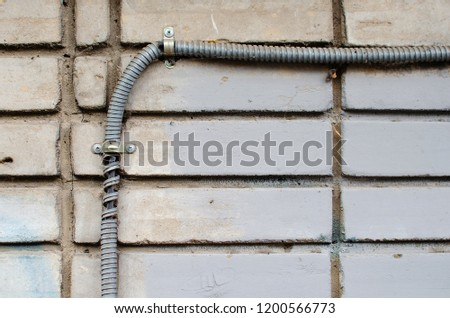 Corrugated wires on the street. Insulated electrical wiring. wire in the corrugation on the carpical wall #1200566773