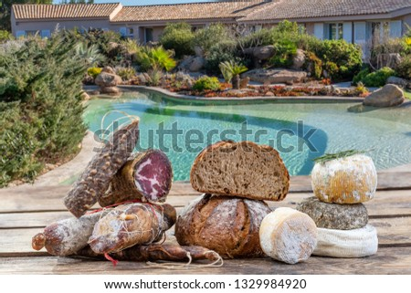 Corsican specialities appetizer: delicatessen, and cheese made in Corsica over a swimming pool panorama background,
