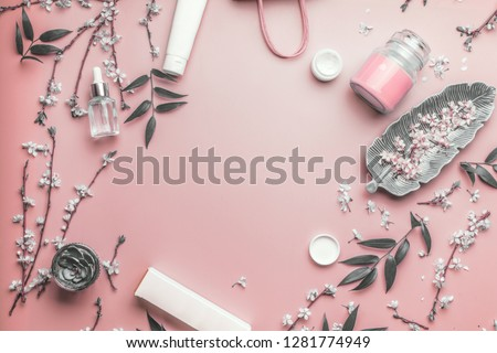 Cosmetic and skin care concept. Various facial cosmetic products on pastel pink background with cherry blossom and leaves, top view, frame. Copy space for your design. Beauty blog layout. Flat lay