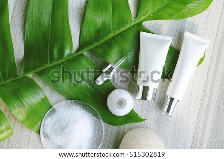 Cosmetic bottle containers with green herbal leaves, Blank label for branding mock-up, Natural beauty product concept. (Color Processed)