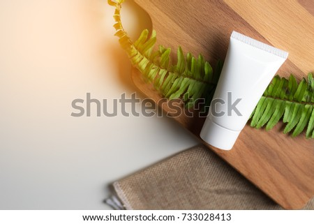 Cosmetic bottle containers with green herbal leaves, Blank label for branding mock-up, Natural beauty product concept.  #733028413