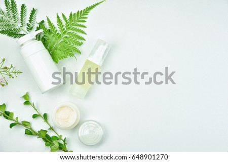 Cosmetic bottle containers with green herbal leaves, Blank label package for branding mock-up, Natural organic beauty product concept. #648901270