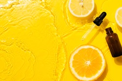 Cosmetic bottle product serum vitamin C with orange and lemon flat lay on yellow background clean water splashing, top view, copy space