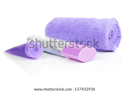 cosmetic bottles, with rolled towel, isolated on white