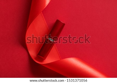Cosmetic branding, glamour lip gloss and shopping sale concept - Luxury lipstick and silk ribbon on red holiday background, make-up and cosmetics flatlay for beauty brand product design