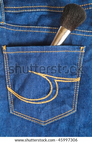 cosmetic brush in jeans pocket, close-up