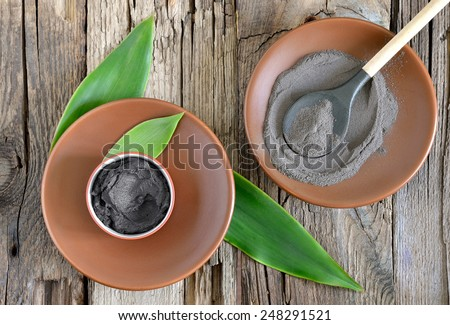 Cosmetic clay in a ceramic bowl decorated with fresh green leaves. Spa body and face treatment