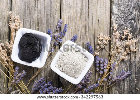 cosmetic clay powder and mud with dried lavender flowers on old weathered wooden table background