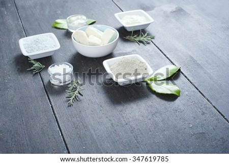 cosmetic clay powder, creams, shea butter and bath salt on old black wood table background