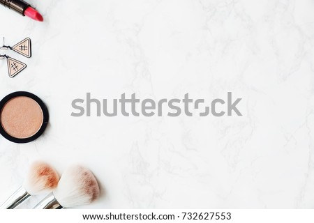 Cosmetic Composition. Pink brush set, lipstick, earring and  eyeshadow palette on marble table. Cosmetic dressing table for women make up concept. Flat lay, top view. Copy space.