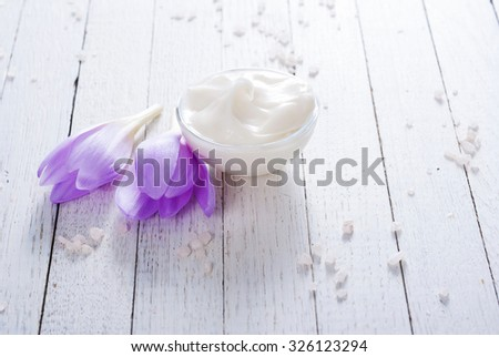 cosmetic cream and autumn crocus herbal flower on white wooden table
