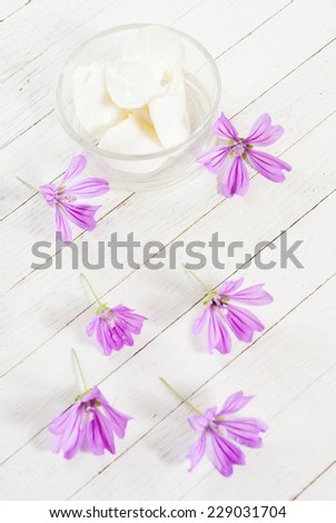 cosmetic cream and flowers on bright wood background