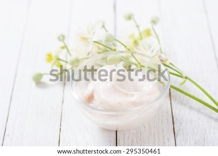 cosmetic cream and white wildflower on bright wood table background