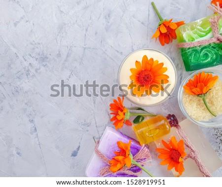 cosmetic cream, calendula flower soap on concrete background