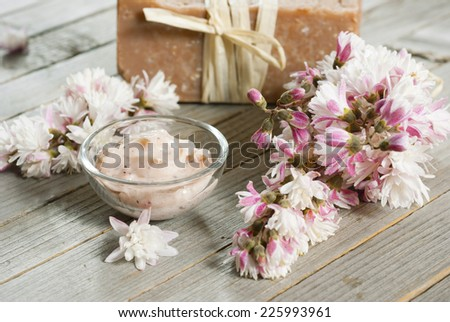 cosmetic cream, soap blocks and flowers on old wood background