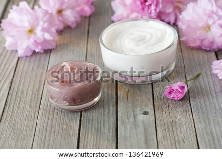 cosmetic cream with japanese cherry blossoms on old weathered wooden table background