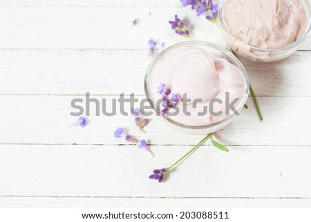 cosmetic cream with lavender flowers on white wood table