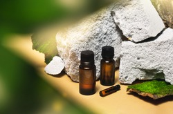Cosmetic essential oil in a dark glass bottles on beige background closeup. Stone podium, moss, tree bark, green leaves. Trendy natural beauty concept. Aroma spa packaging clipart