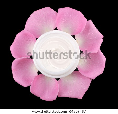 cosmetic face cream on a black background with rose petals