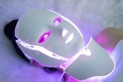 Cosmetic face mask. the girl is wearing a mask. Promotional Products. health and beauty of the face. LED Facial Mask, Beauty Photon Therapy. LED mask regenerative treatment applied to a young woman