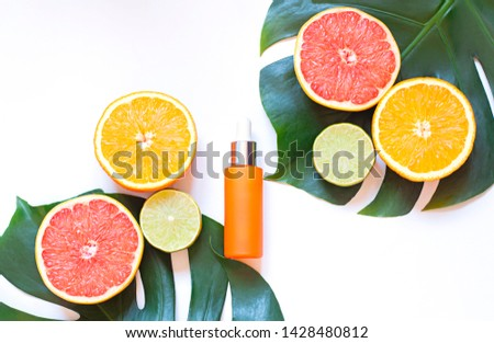 Cosmetic flat lay with vitamin C serum and citrus on the white background. Top view