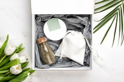 Cosmetic gift set of body or face cream container and bag with soap and a bottle of bath salts. Tulip flowers and palm leaf near box on white marble background, flat lay or top view