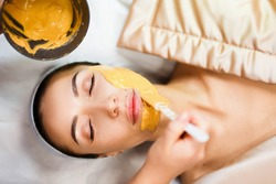 Cosmetic jelly mask, facial skincare. Cosmetologist applies yellow gold alginate mask with spatula on face of a woman. Facial skin treatment in the beauty salon. Top View above