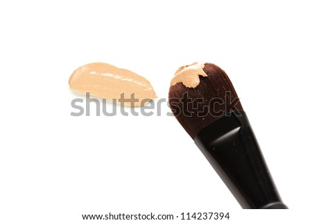 Cosmetic liquid foundation and brush isolated on white