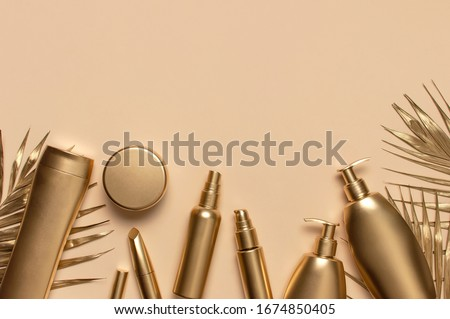 Cosmetic mock up gold bottles. Cosmetics Branding Concept. Cosmetic containers, golden tropical palm leaves on beige background. Flat lay top view copy space. Cosmetic products, beauty background