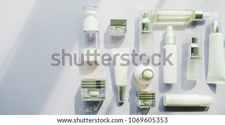 cosmetic packaging set on purple background. group of skincare cream serum oil . facial beauty cosmetic spa product. natural cosmetology concept skin treatment with green leaf and laboratory science . #1069605353