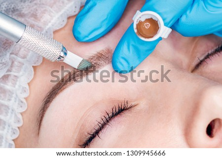 Cosmetic procedures for the treatment of eyebrows. Microblading in the beauty salon. Professional cosmetology. The process of applying the pigment.