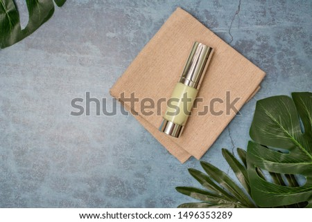 cosmetic product and tropical leaves on concert background, cosmetic product