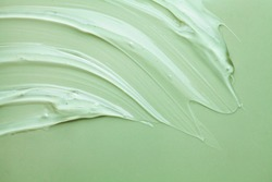 Cosmetic product creamy gel texture smudge on pastel green sage colored background