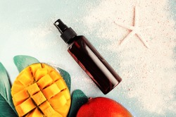 Cosmetic product in spray bottle top view summer skin care background, mango fruit, beach sand, pastel toned. Summertime beauty treatment, safe, natural, and aromatic
