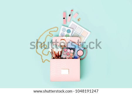 Cosmetic products flowing from Makeup bag on pastel blue background.  Flat lay, top view. Fashion concept #1048191247