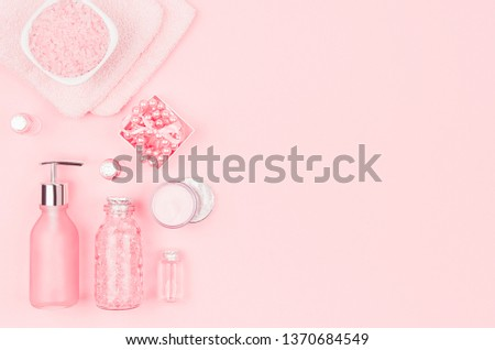 Cosmetic products for bathroom, health and hygiene in modern girlish style - soap, bath salt, essential oil, cream, towel, perfume, pearls on pink background. #1370684549