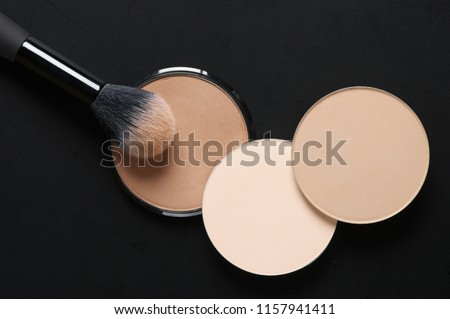 Cosmetic set of various shades compact face powder and makeup brush on black background. Top view point, flat lay.