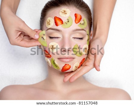 Cosmetician doing fruit mask on a face of beautiful young woman - indoors