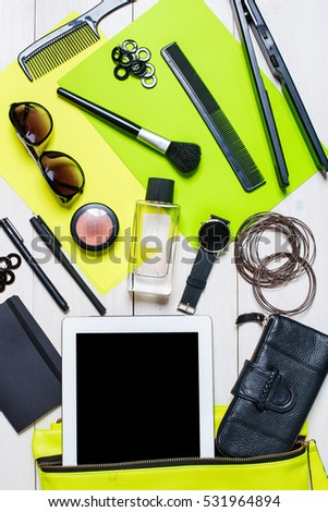 Cosmetics and women\'s accessories fell out of the green handbag on white background.