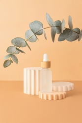 Cosmetics bottle with dropper stay on the podiums.Empty pedestal near it for showing products.Earth tones,pastel isometric backdrop.Zero waste packaging,copy space.Good as advertisement banner.