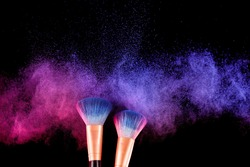 Cosmetics brush and explosion colorful makeup powder background