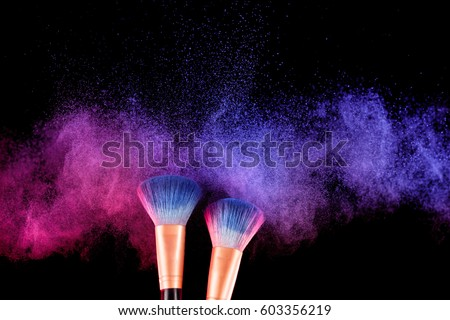 Cosmetics brush and explosion colorful makeup powder background #603356219