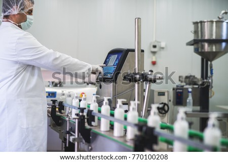 Cosmetics fabric worker typing on fabric production computer while liquid soap going on a production line. #770100208