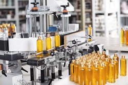 Cosmetics factory. Bottling line filled with yellow shampoo. Automated process on factory. Line of bottles filled with yellow substance going on conveyor to be twisted. Research, innovation, creation