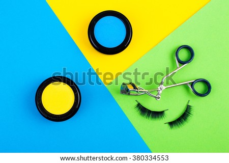 cosmetics for makeup. bright blue background with green eyelashes glamorous and trendy