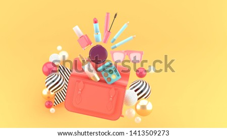 Cosmetics from the handbag surrounded by colorful balls on an orange background.-3d rendering.