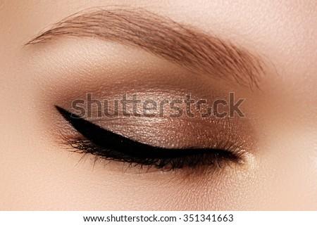 Cosmetics & make-up. Beautiful female eye with sexy black liner makeup. Fashion big arrow shape on woman\'s eyelid. Chic evening make-up