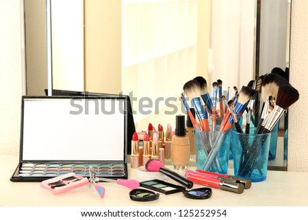 cosmetics on table near mirrow